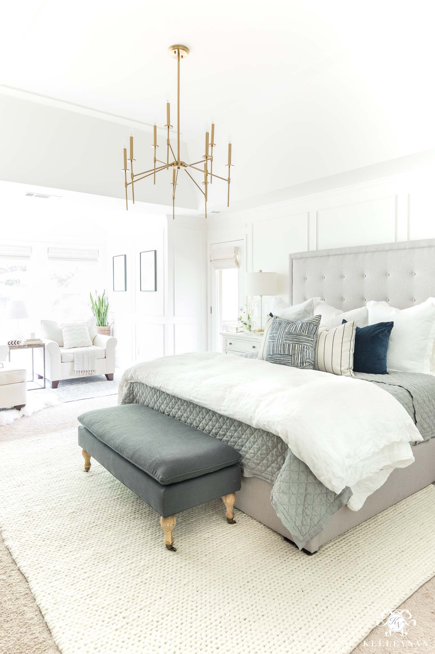 Neutral master bedroom design ideas with gray tufted headboard and brass chandelier