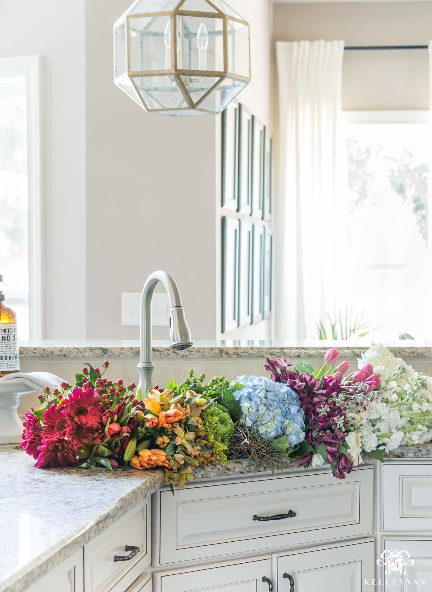 Rainbow flower assortment in the kitchen sink for centerpiece ideas