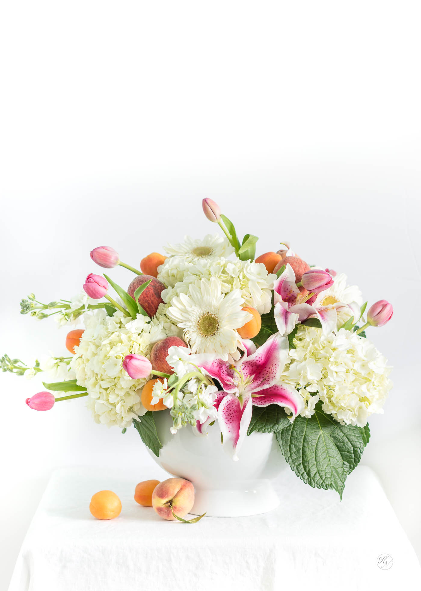 How to create a fruit and floral centerpiece with peaches, apricots, and pink and white flowers