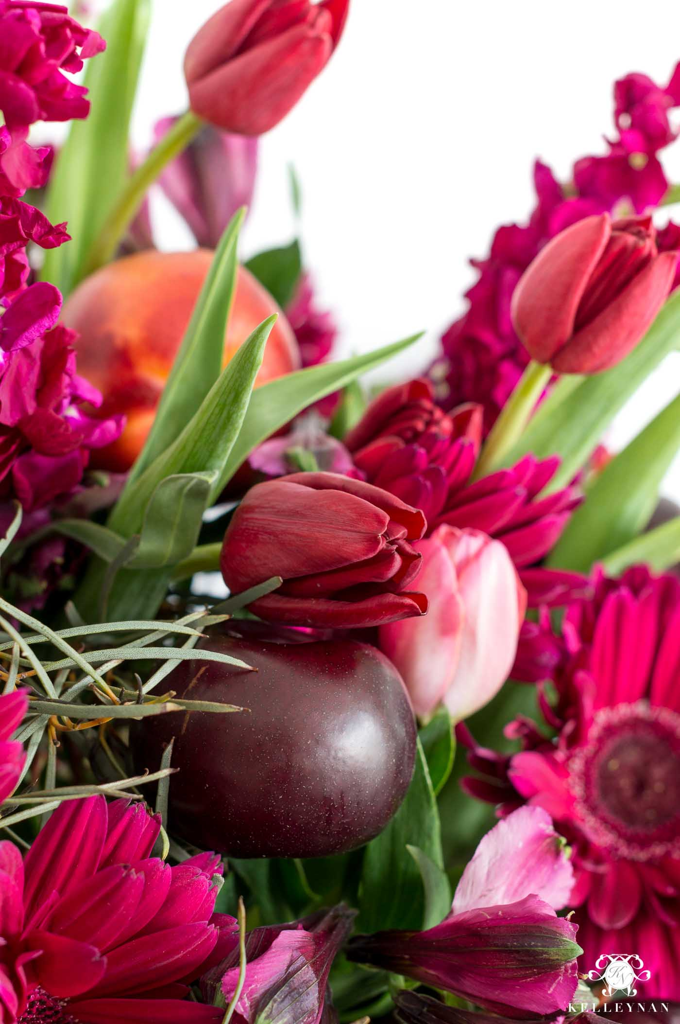 Fruit and flower combinations to create a stunning centerpiece with pink, purple, and red flowers and plums