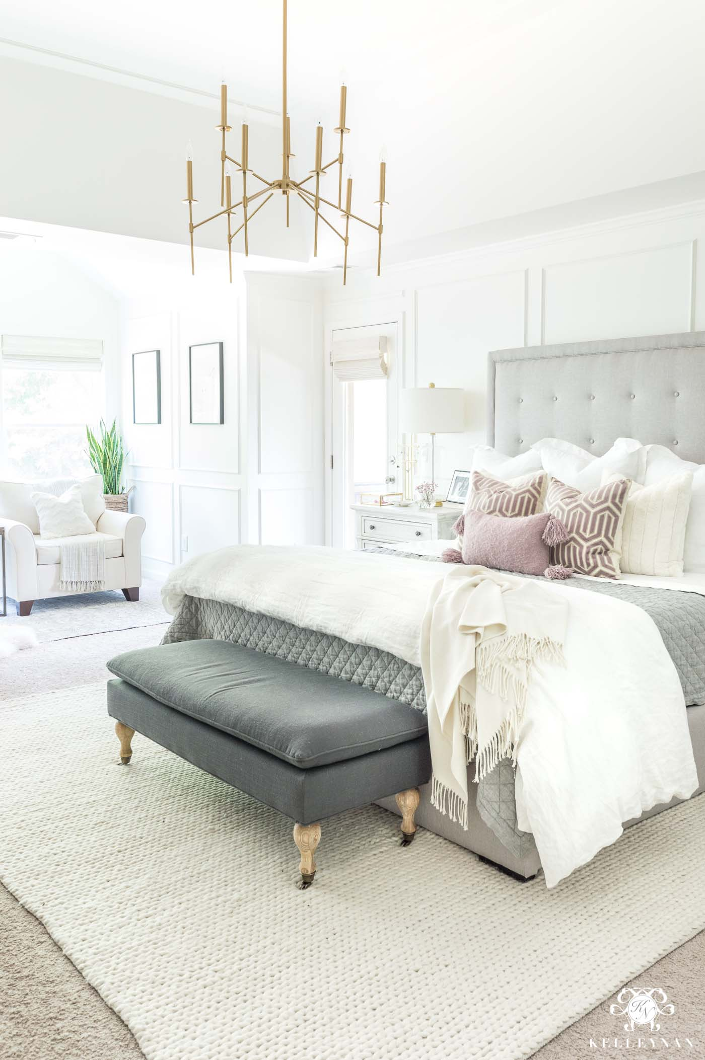 Mixing and matching bedroom furniture and tying together a neutral master retreat with a gray tufted bed and blush pillow accents