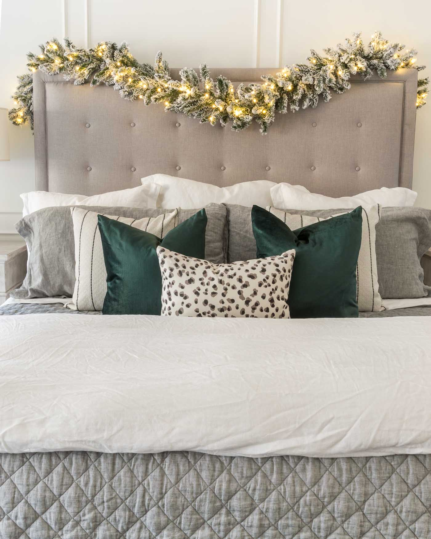Christmas Decor Ideas for the Bedroom- Garland and Lights Draped Over Tufted Headboard