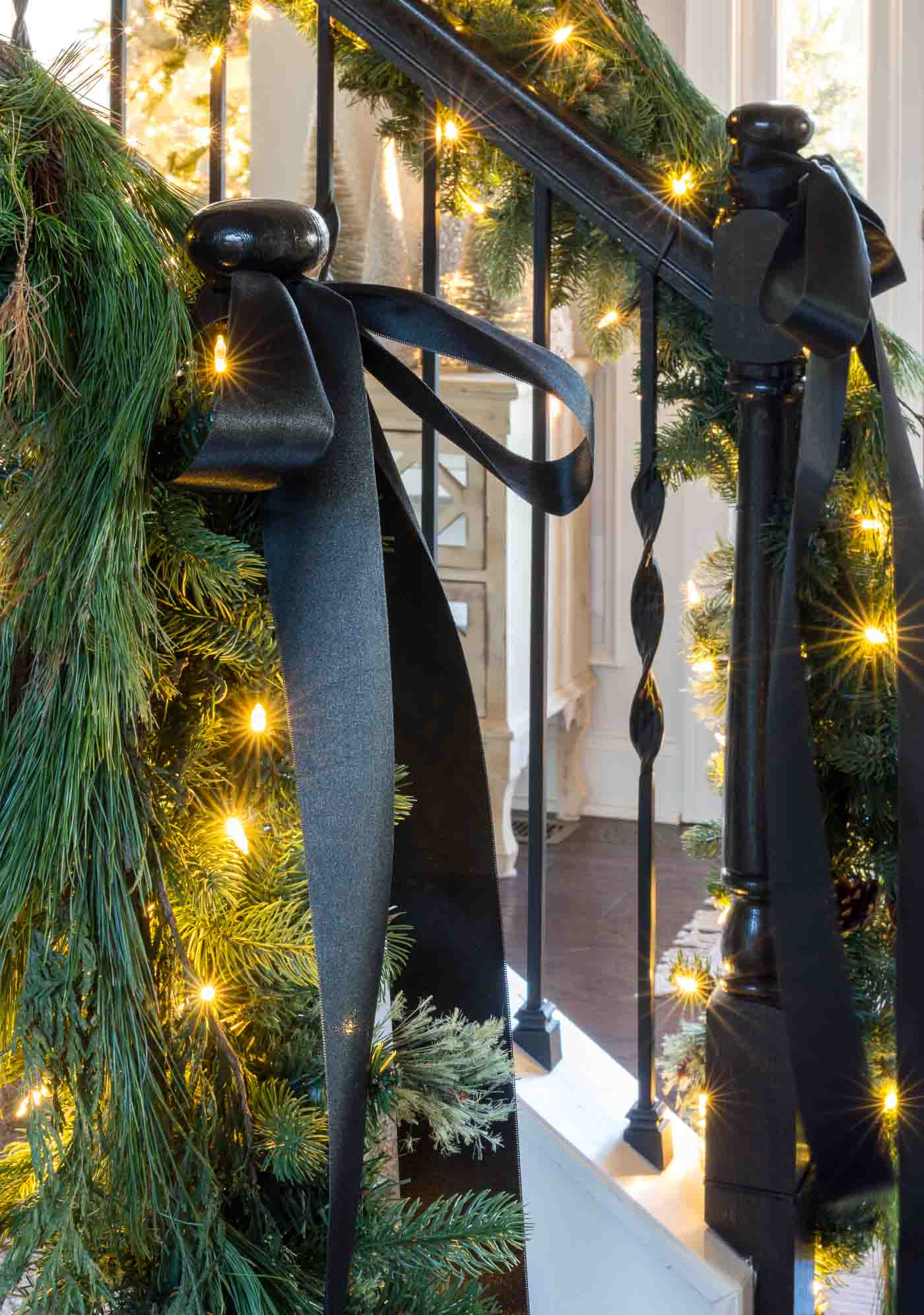 How to decorate a stair banister with greenery and Christmas garland with black satin ribbon