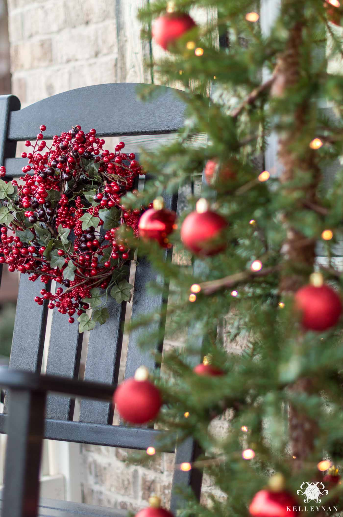 Front porch Christmas decorations and red berry wreaths on rocking chairs