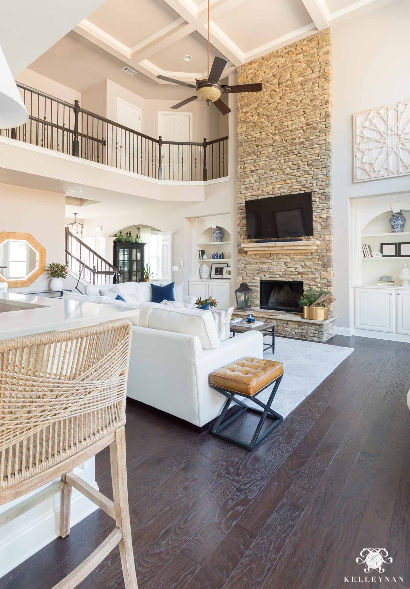 Classic, pretty living room with white sofas and tall stacked stone fireplace