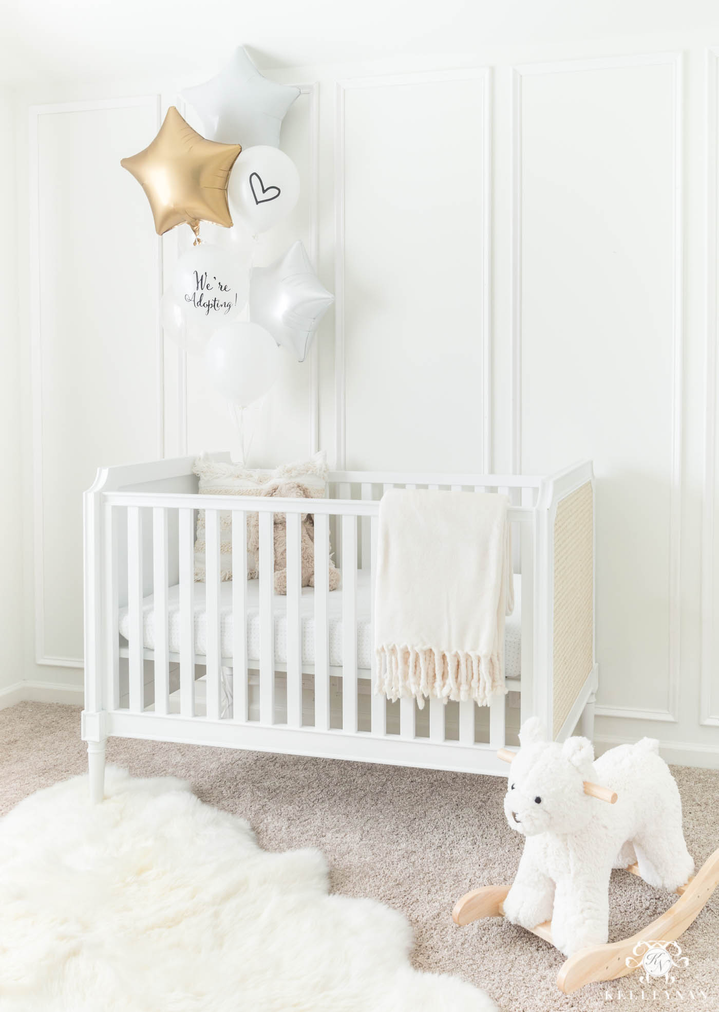 Baby adoption announcement idea using a nursery crib and balloons