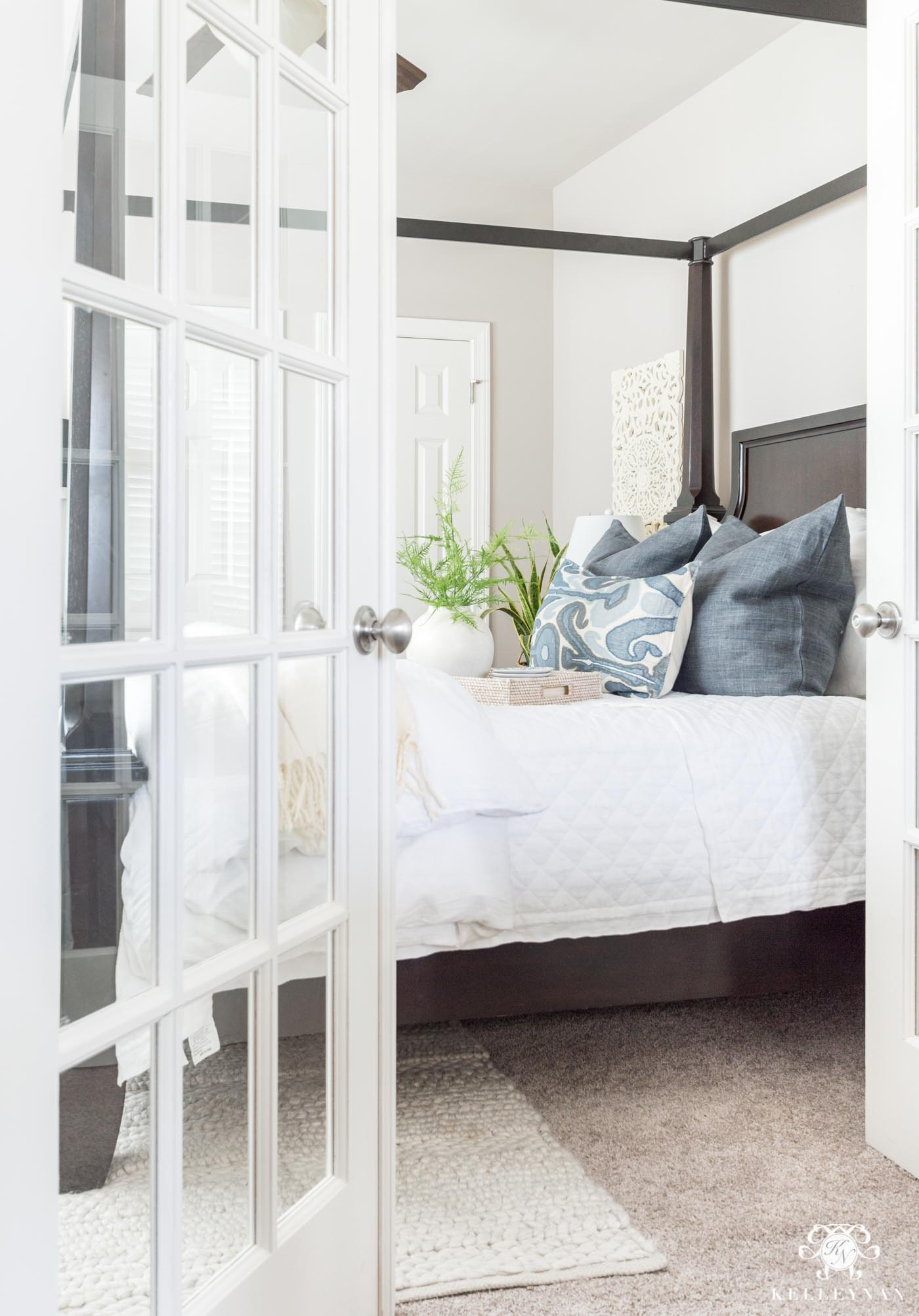 Guest bedroom canopy bed with blue and white classic bedding