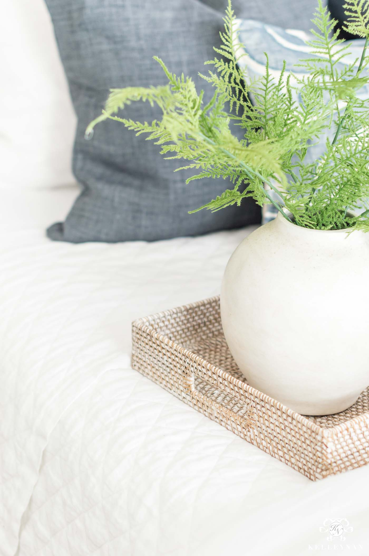 white vase with greenery and asparagus ferns