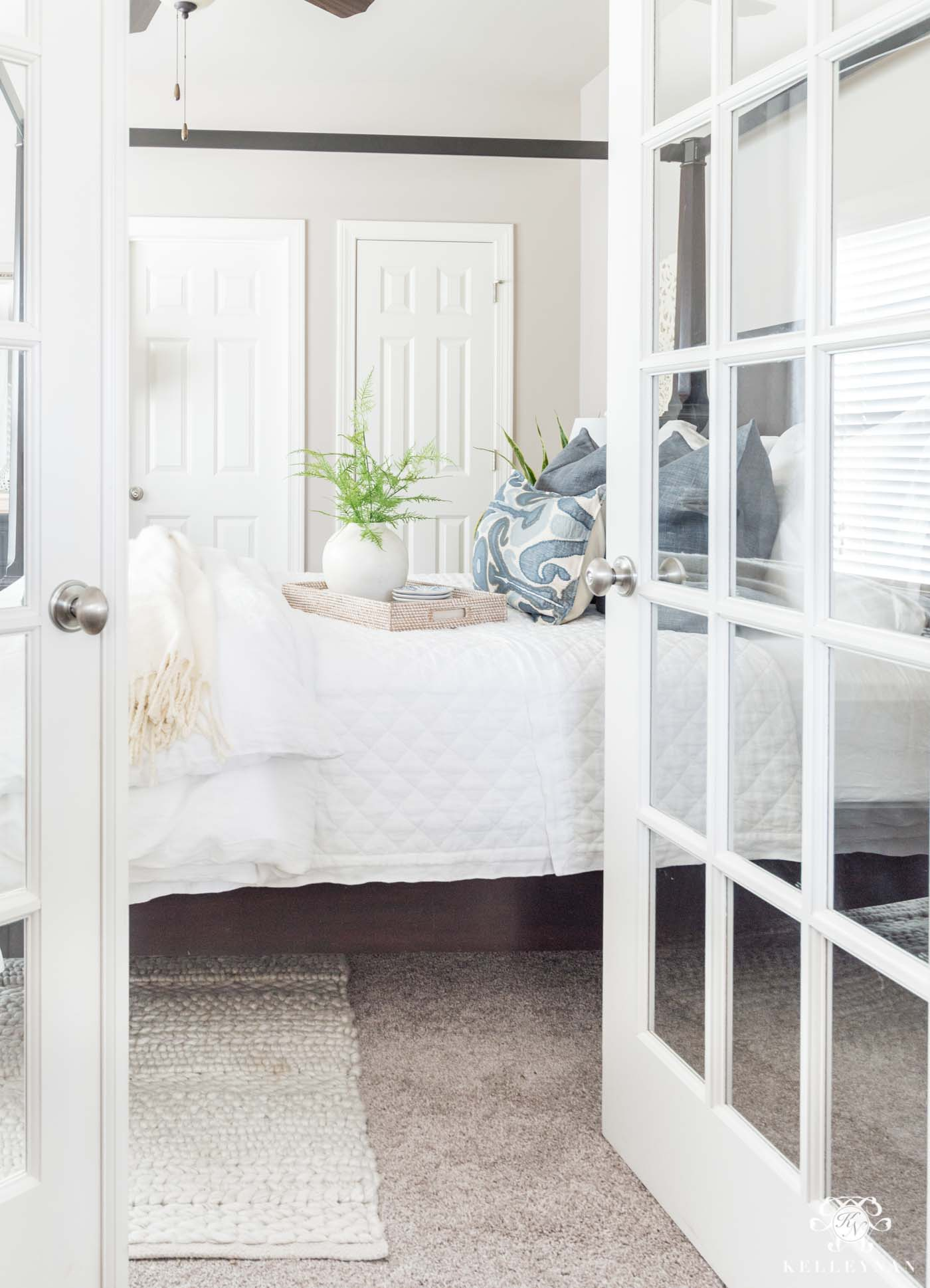 French doors leading to a blue and white guest bedroom