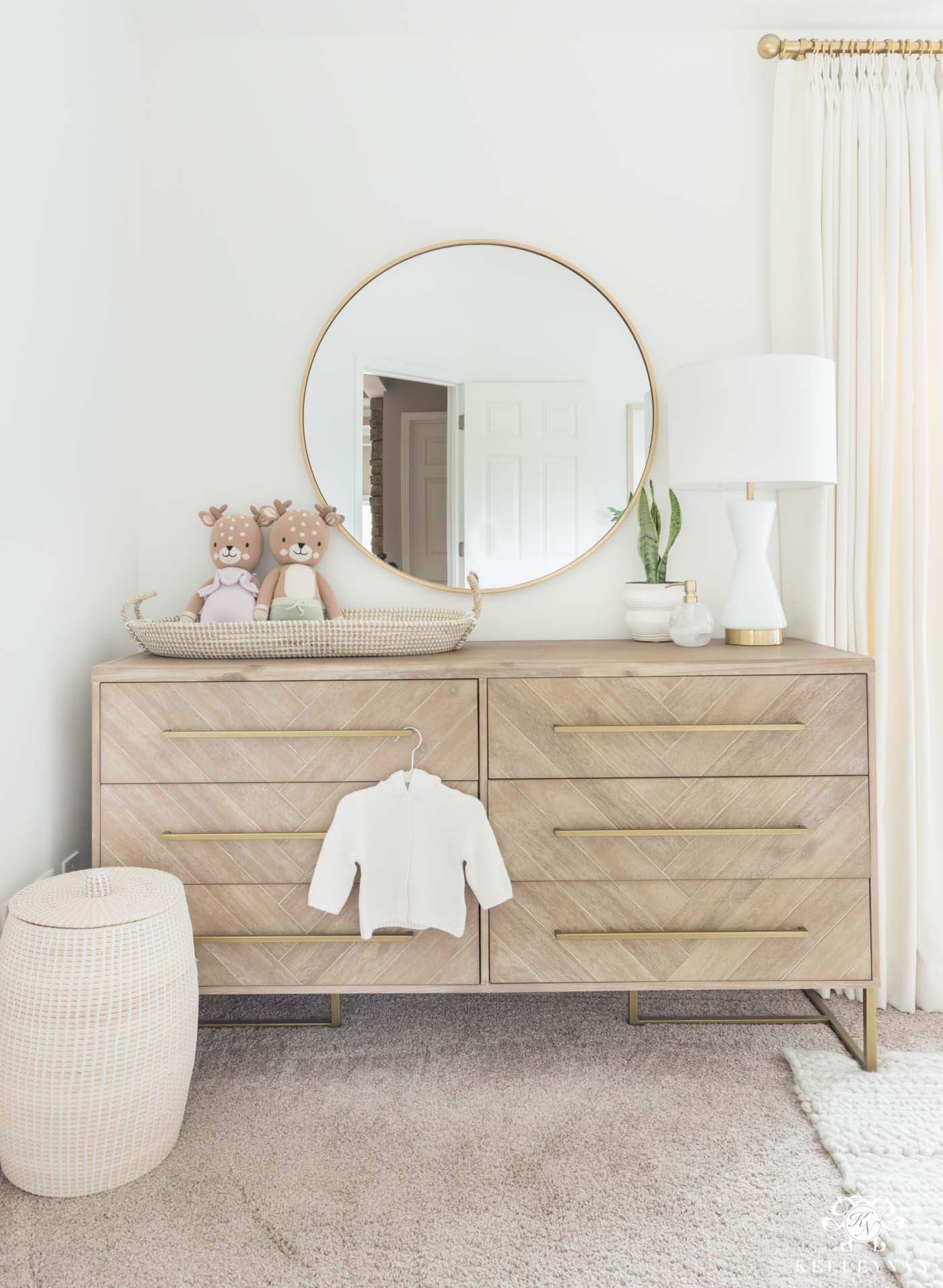 Nursery changing station on a double dresser with pretty woven changing basket
