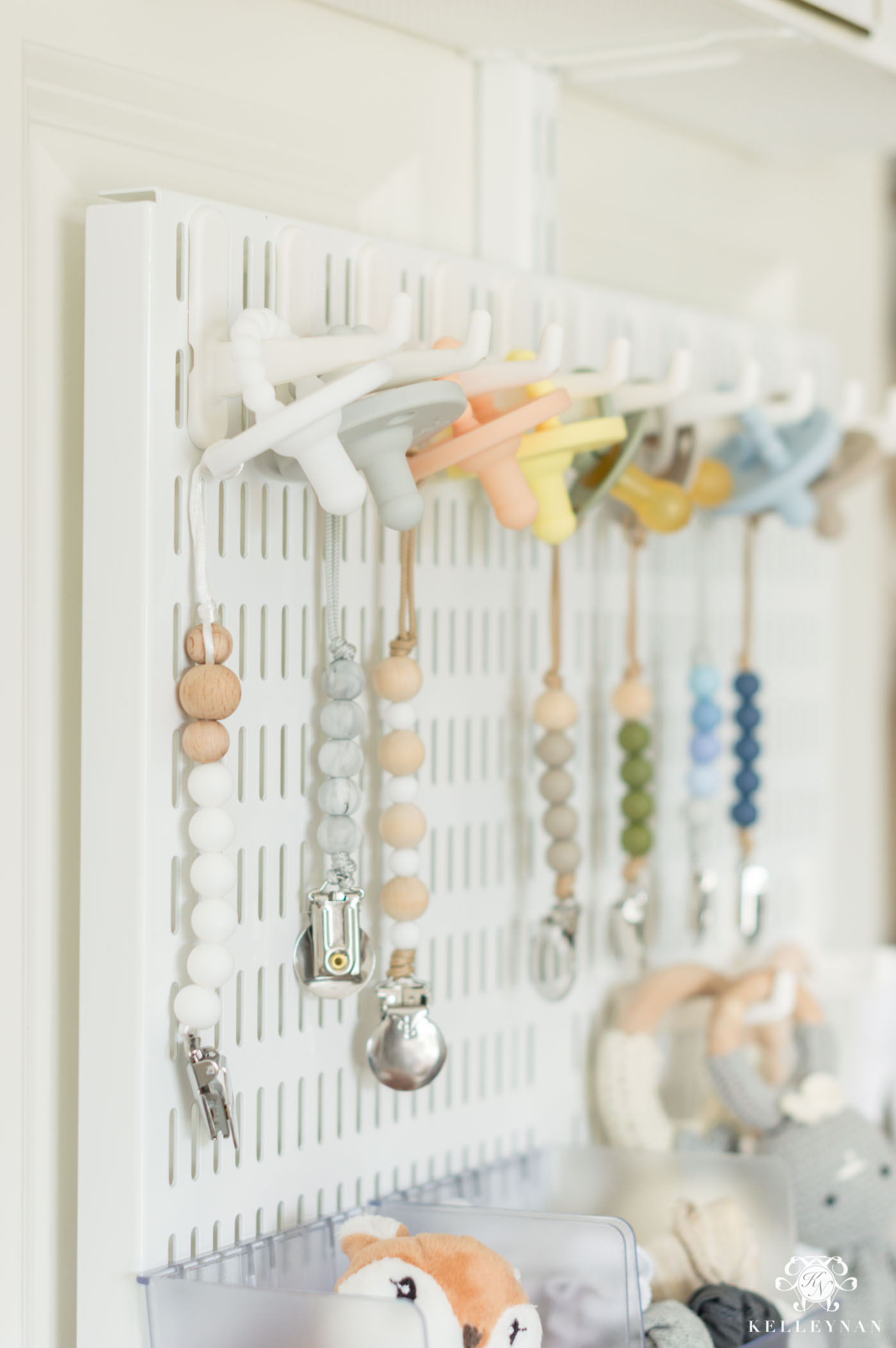 pacifier and pacifier clip organization on the back of the closet door