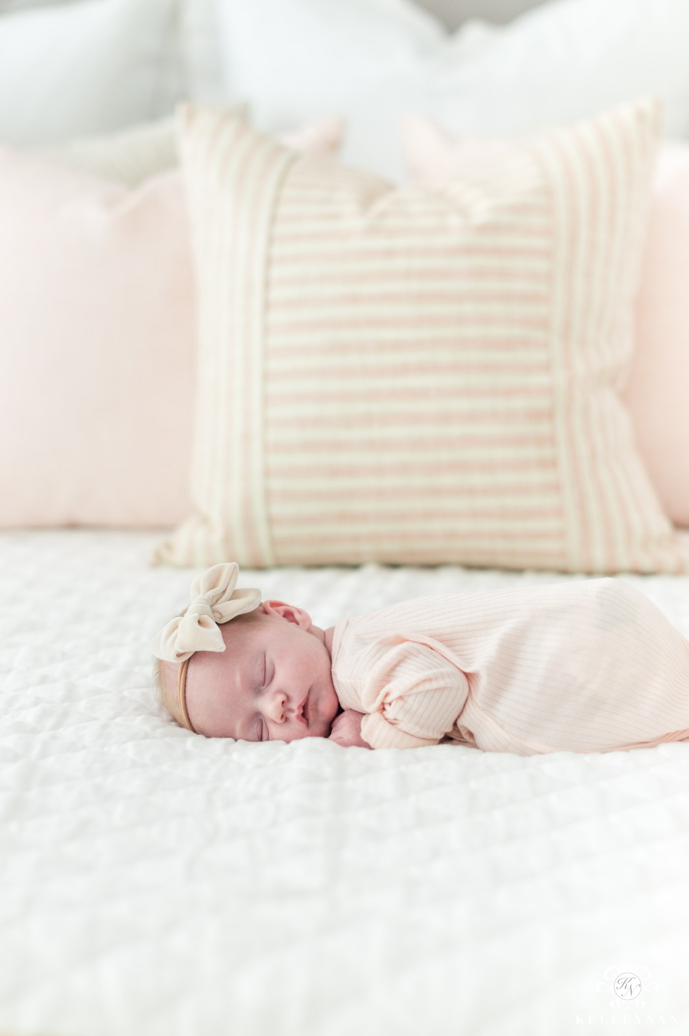 Little girl newborn photo with white and pink bedding