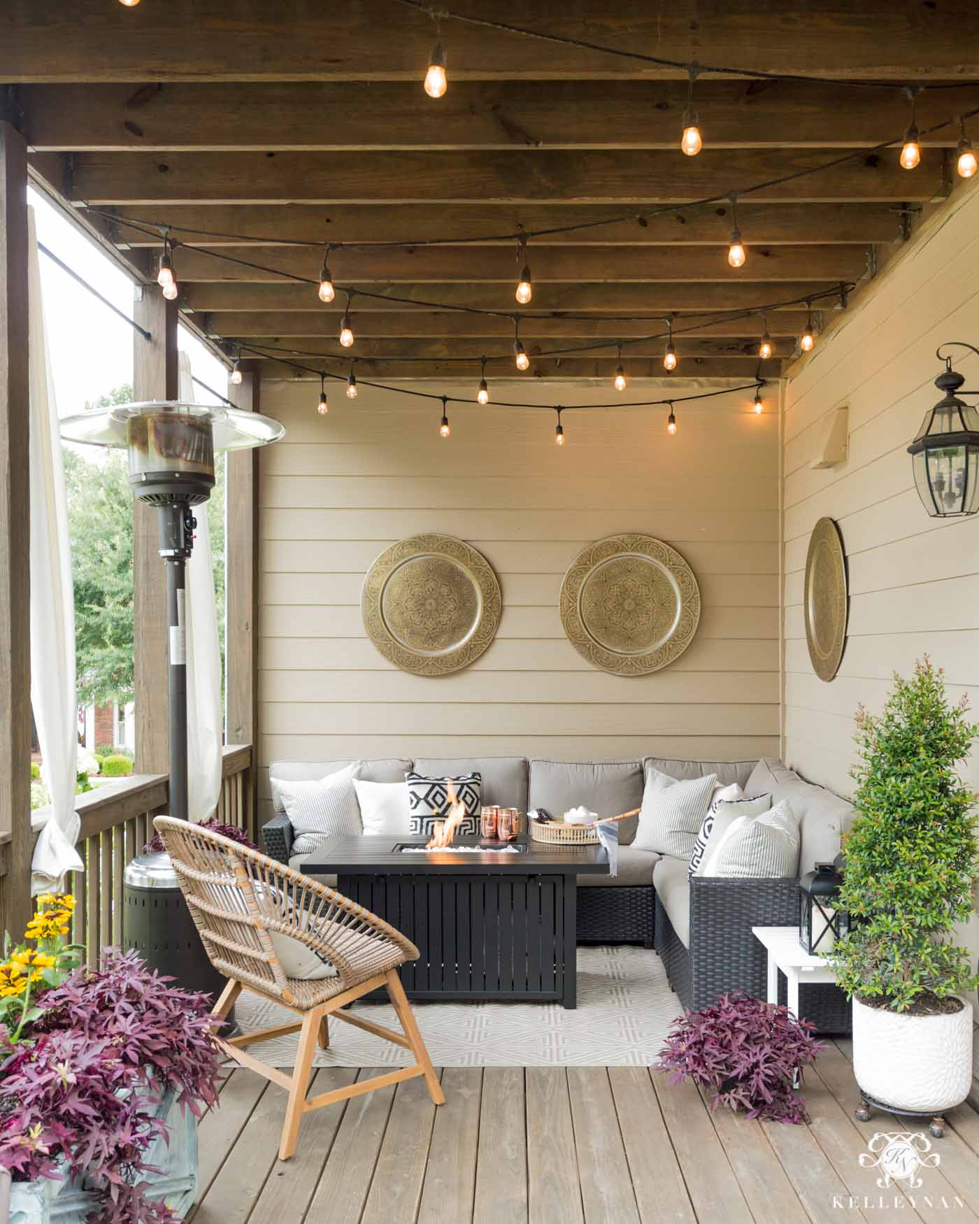 Summer to fall outdoor living decor with twinkle lights, a heat lamp, and fire pit table