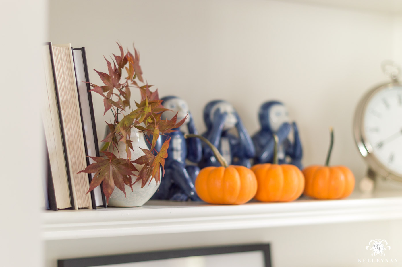Fall shelf decor in the living room with orange pumpkins and maple leaves