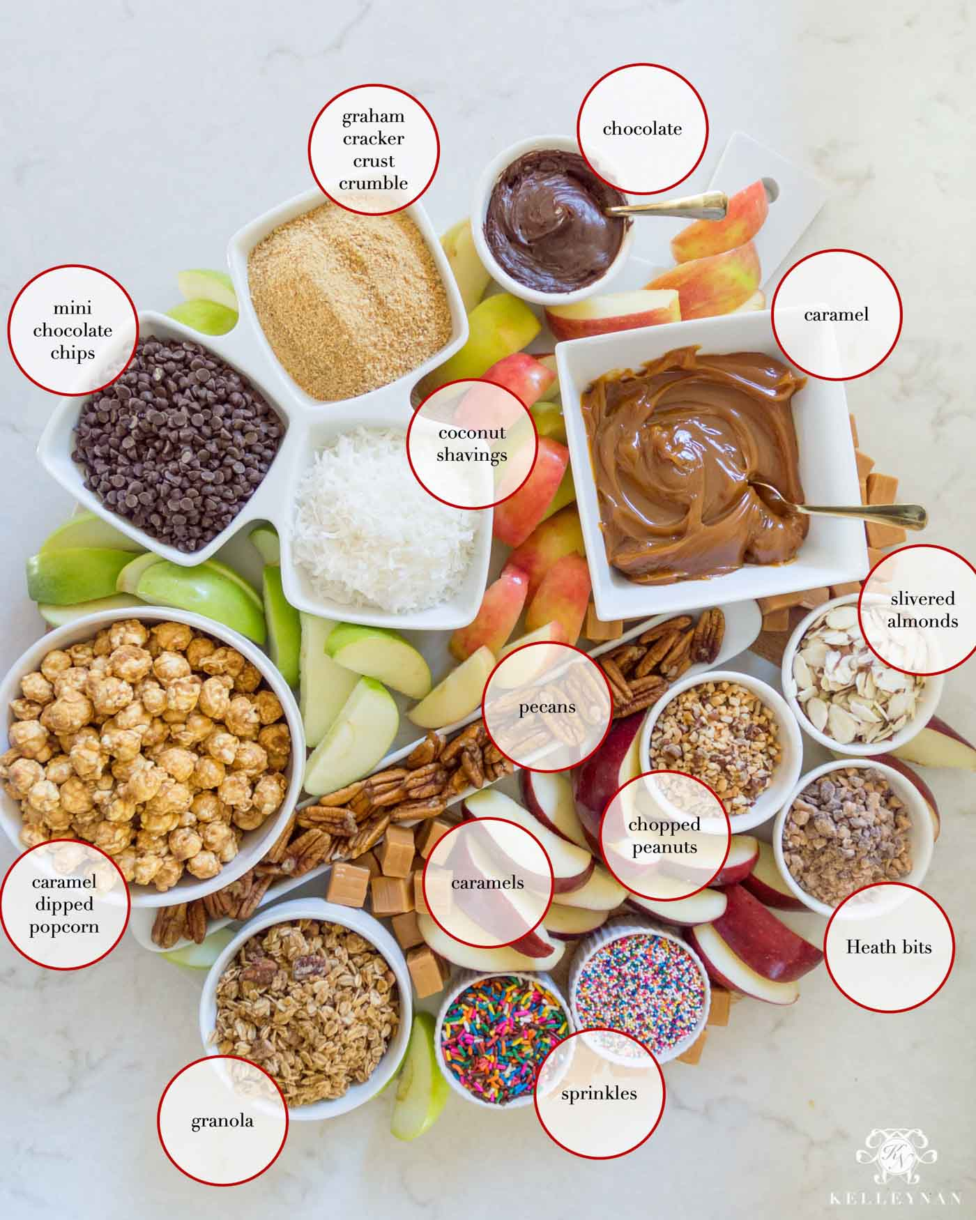 Sliced caramel apples and all the toppings for a fall caramel apple board