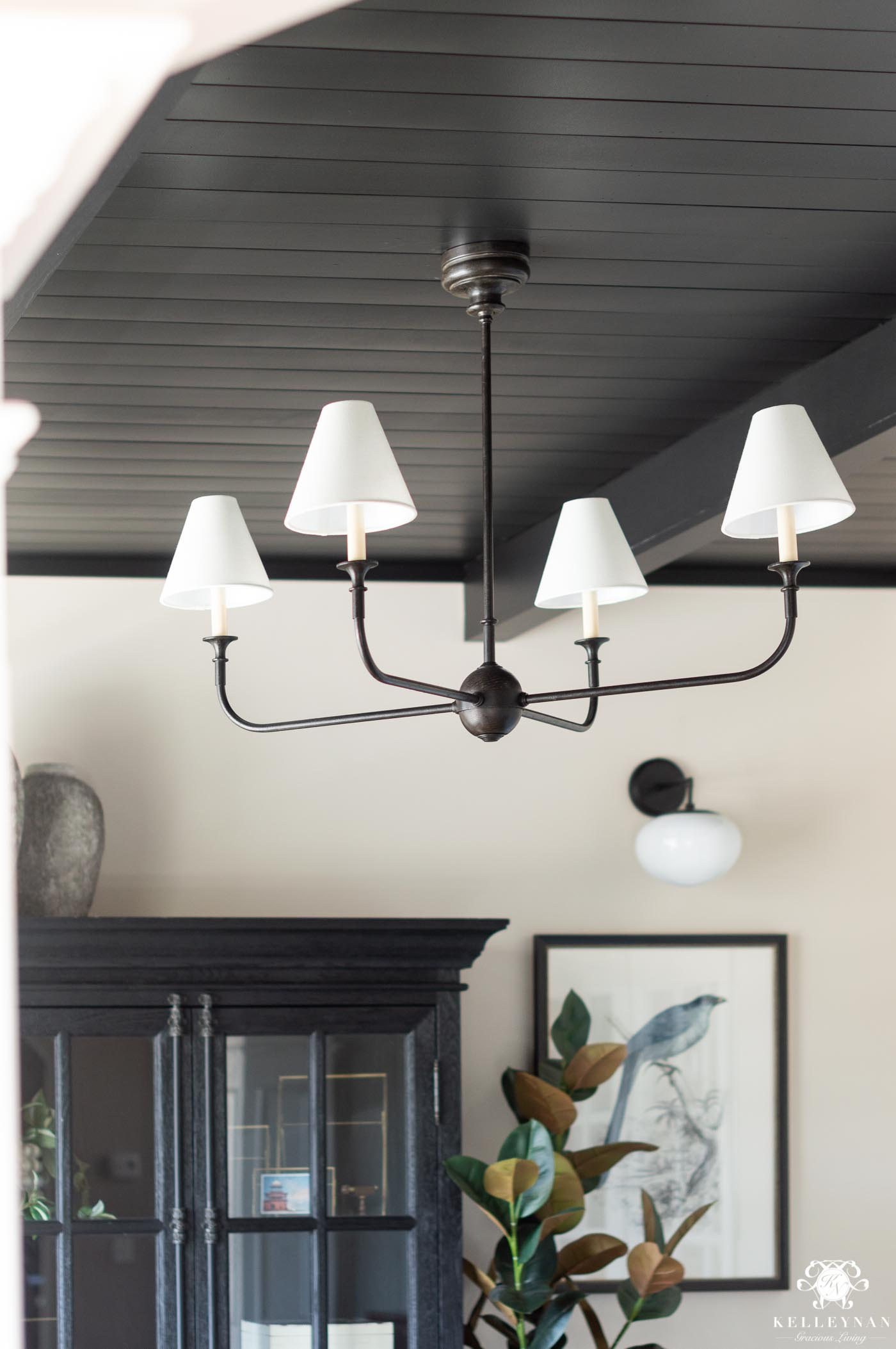statement chandelier with a black planked shiplap ceiling with black beams